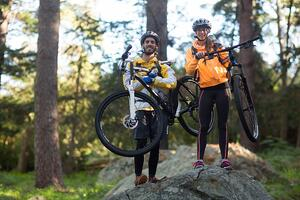 Portrait of biker couple carrrying mountain bike in countryside forest