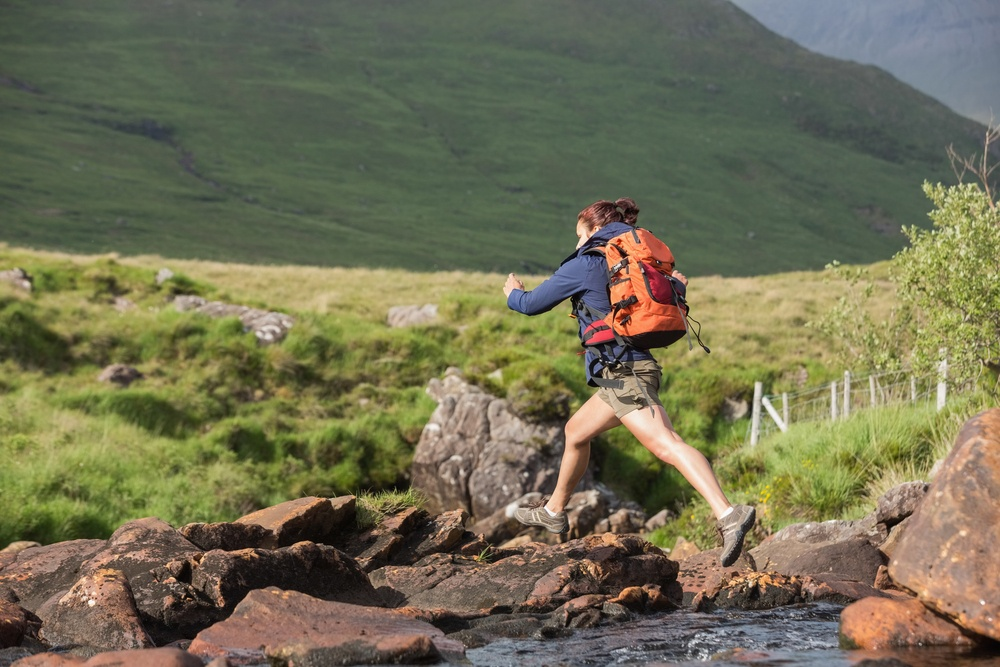 Athletic hiker leaping across rocks in a river in the countryside