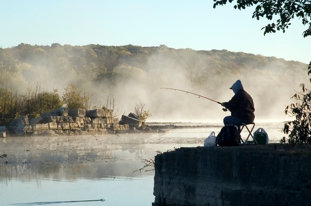 Fisherman by misty lake